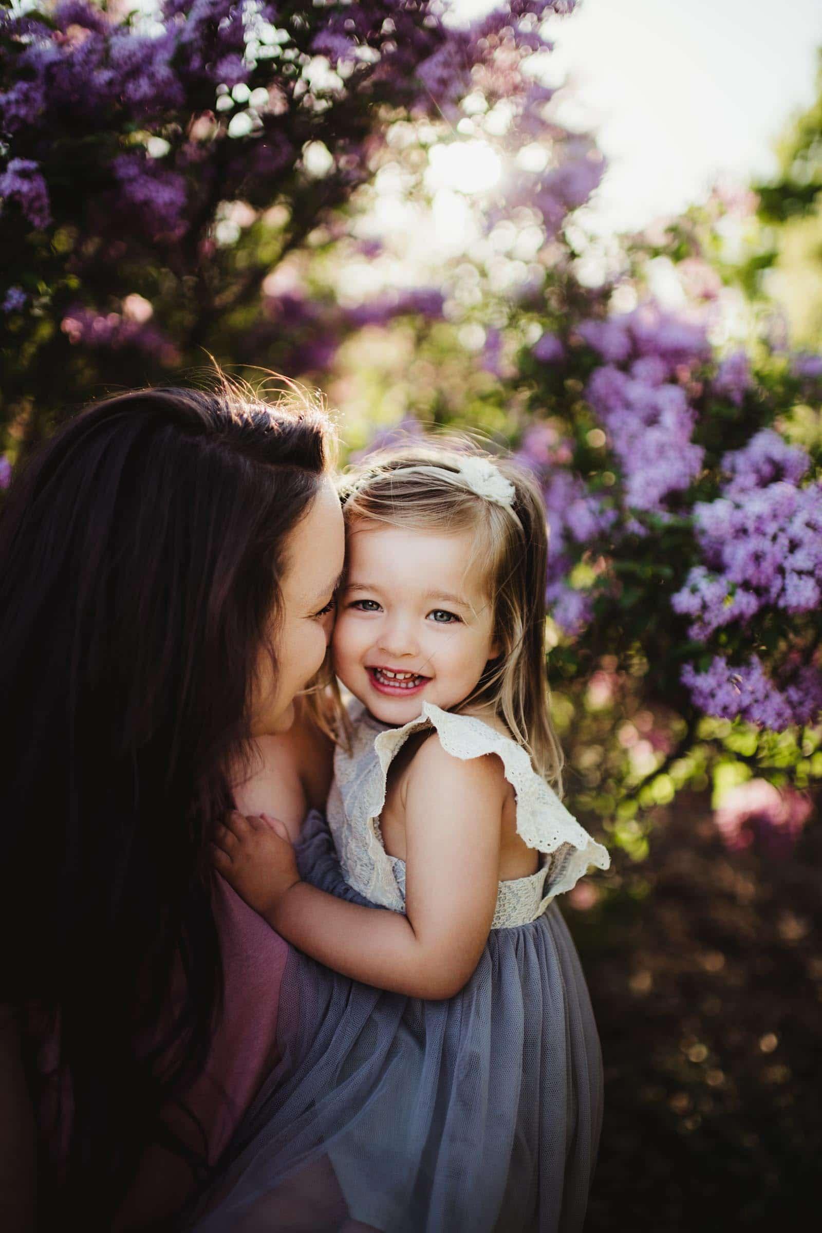 Mom Snuggling Little Girl Purple Flowers