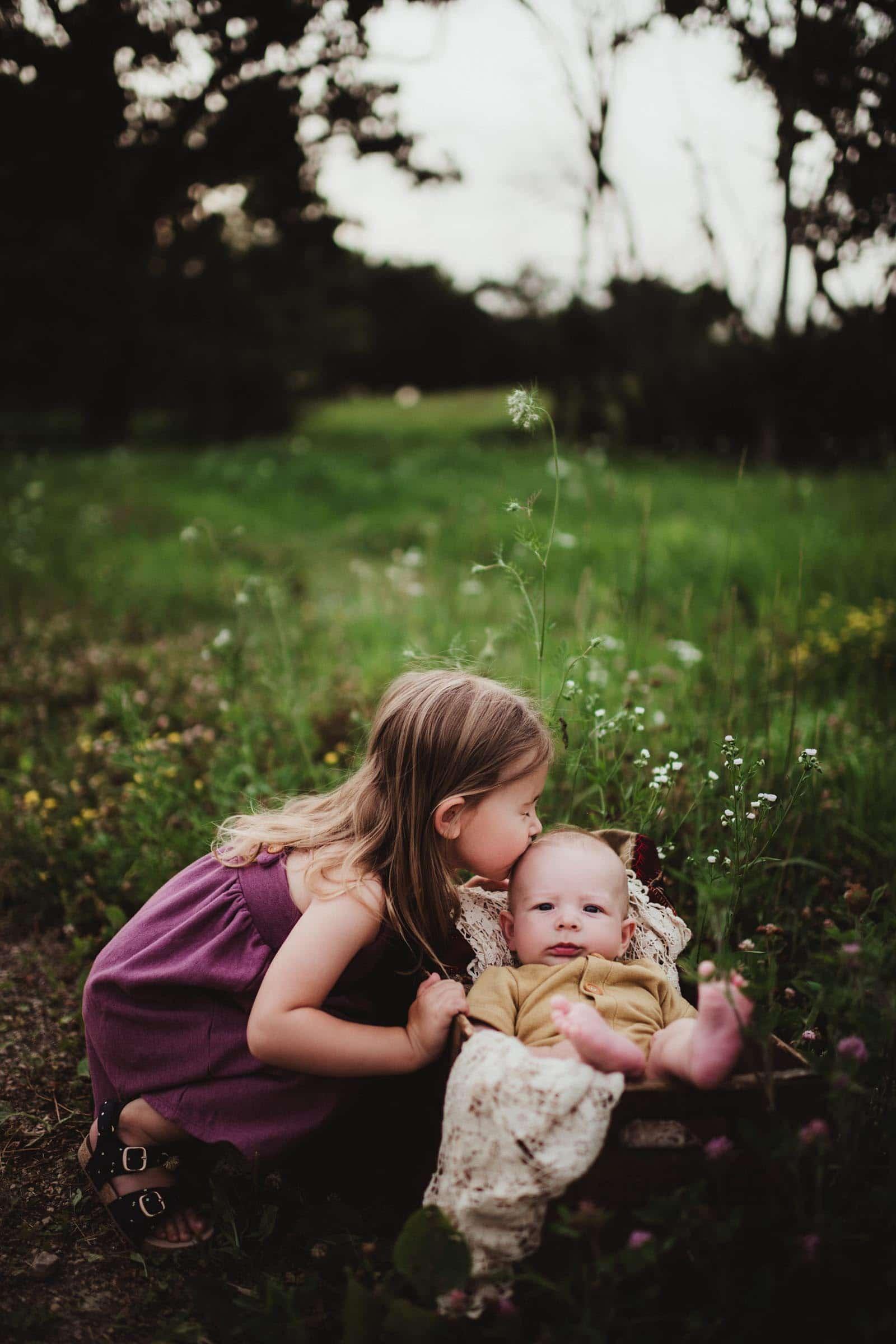Little Girl Kissing Baby Sibling in Field