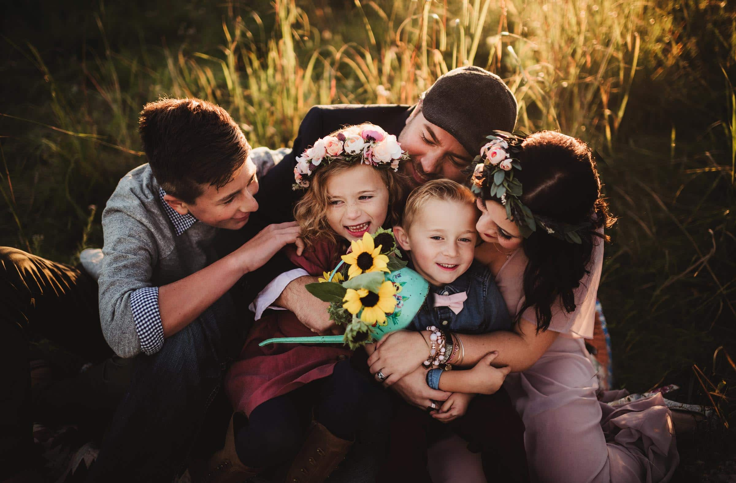 Family Snuggling Holding Sunflowers