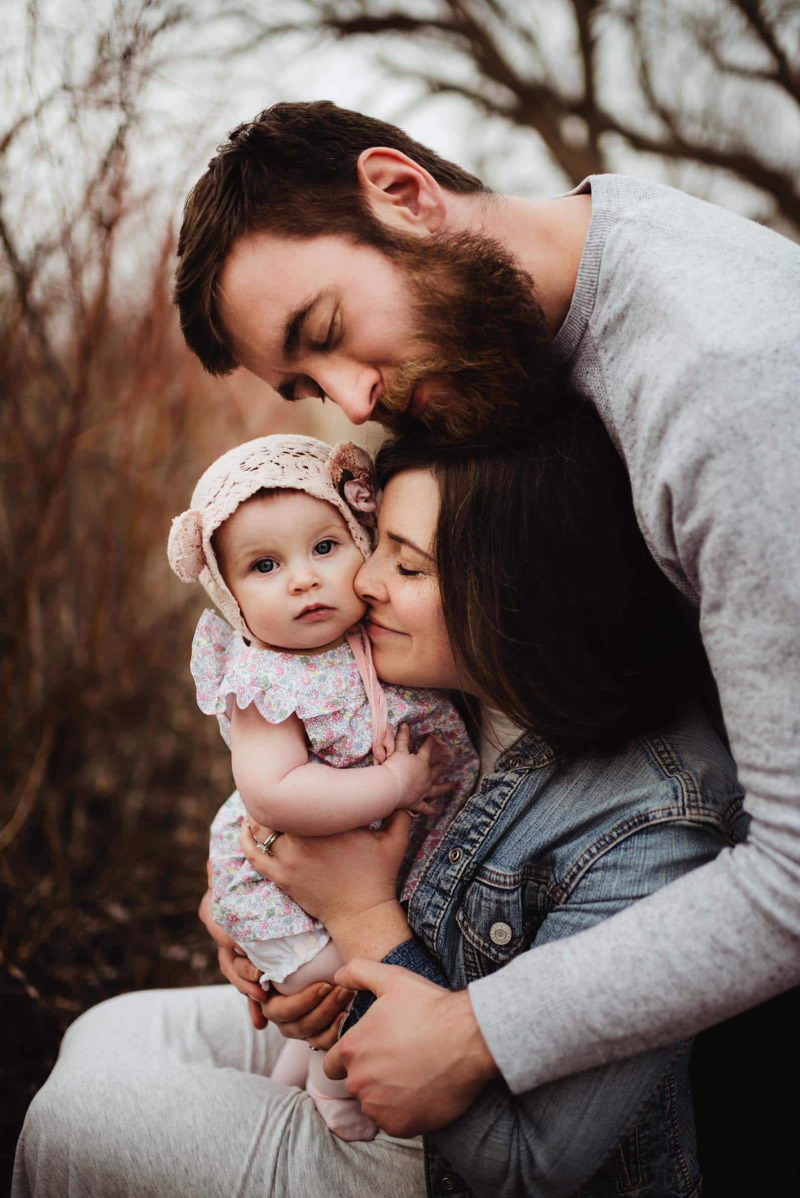 Parents Snugging Little Girl in Hat