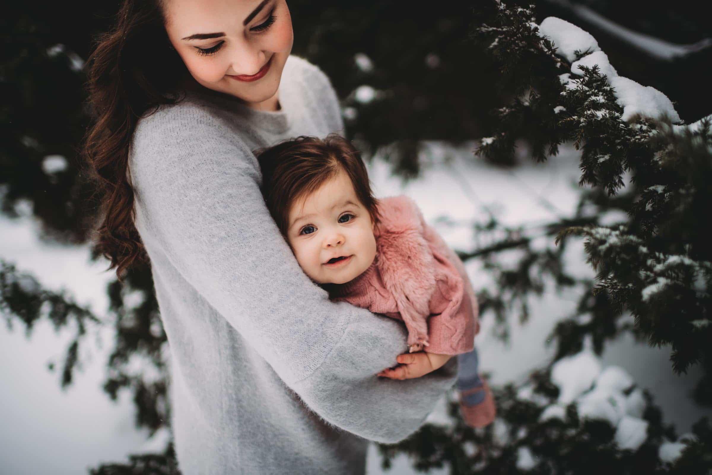 Mom Holding Little Girl in Snow