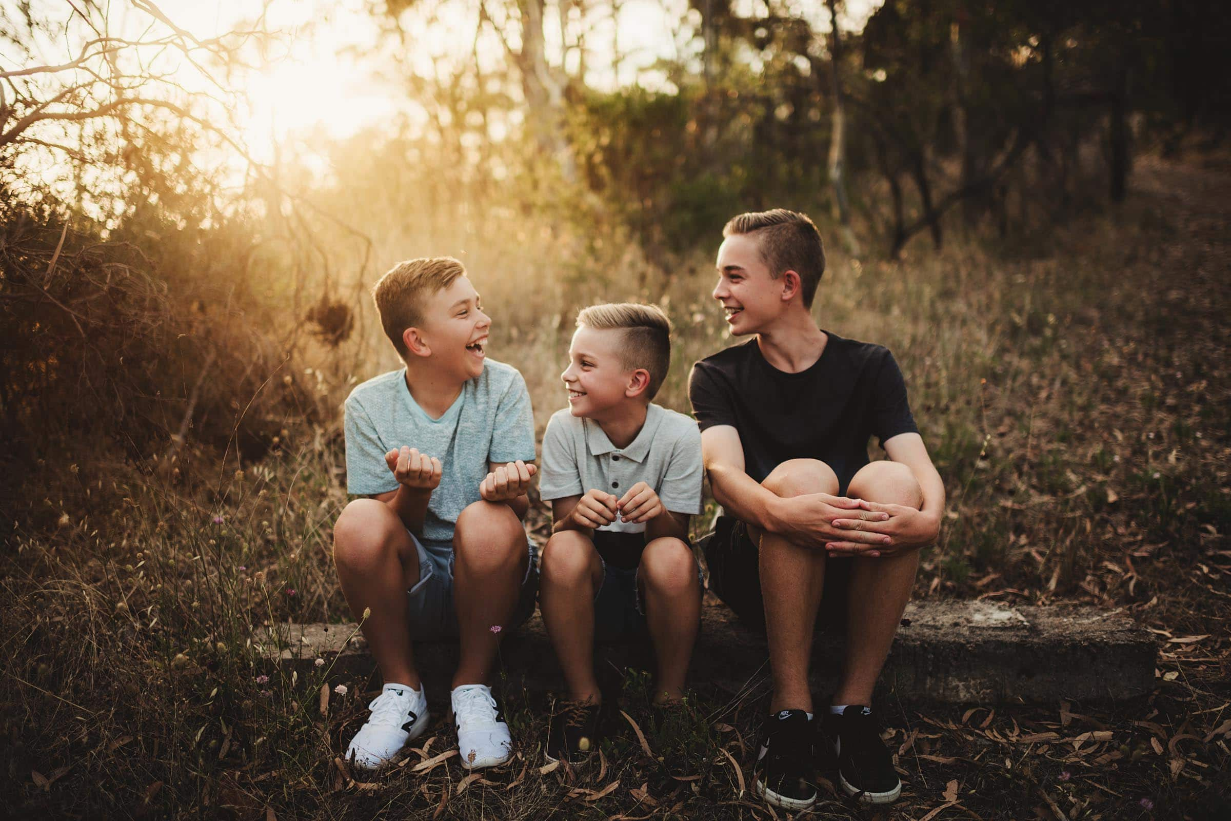 Three Brothers Sitting on Log Laughing