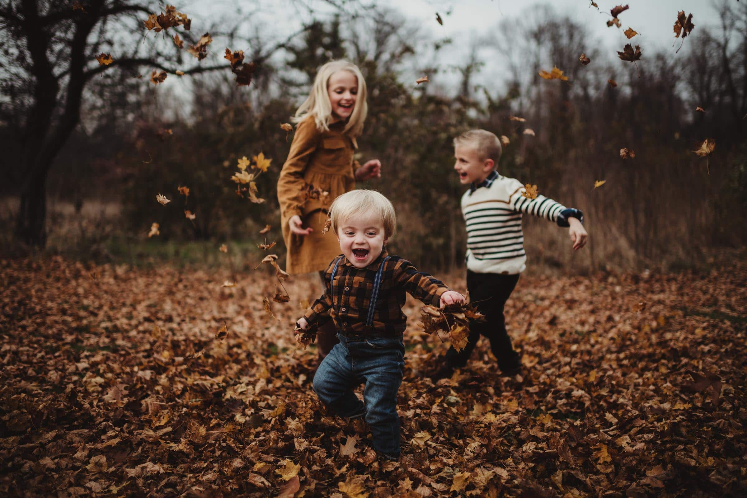 Three Kids Playing in Leaves
