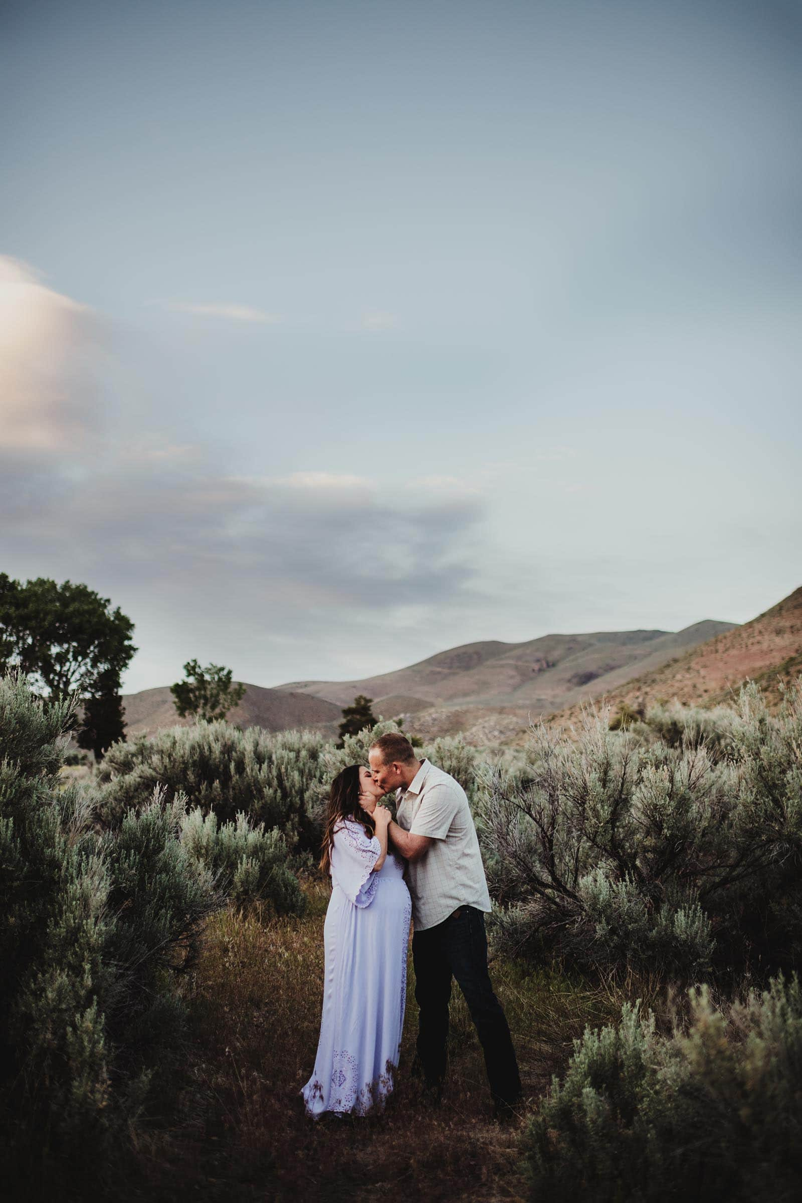 Maternity Couple Kissing in Field