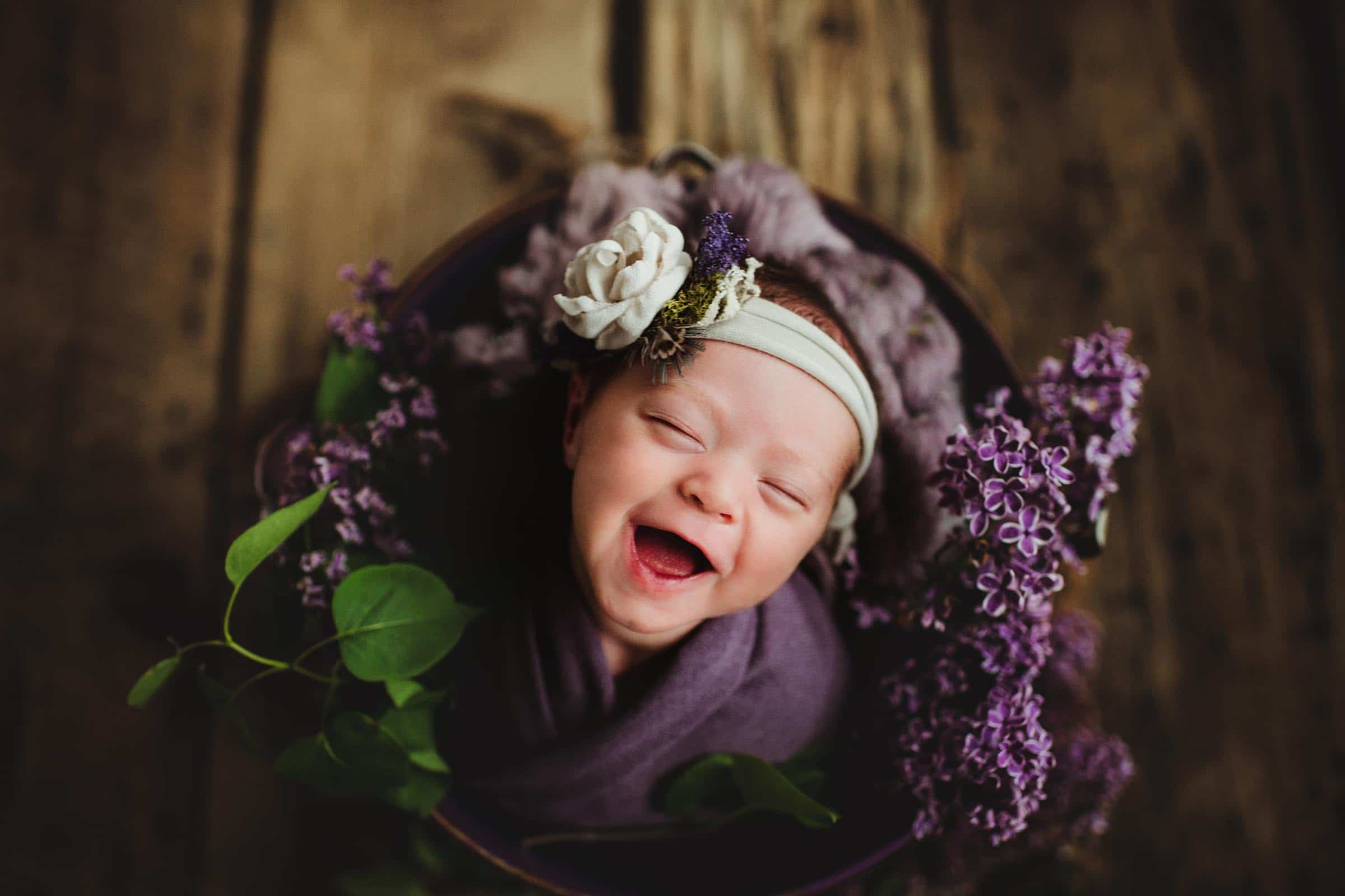 Newborn Girl in Purple Laughing