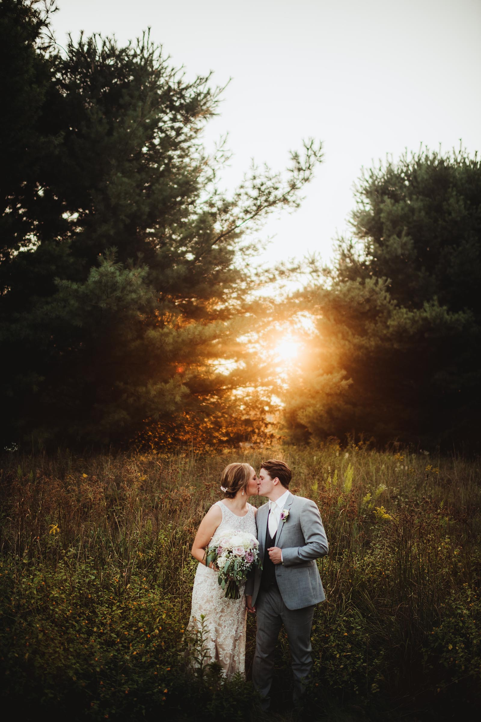 Bride Groom Kissing in Field at Sunset