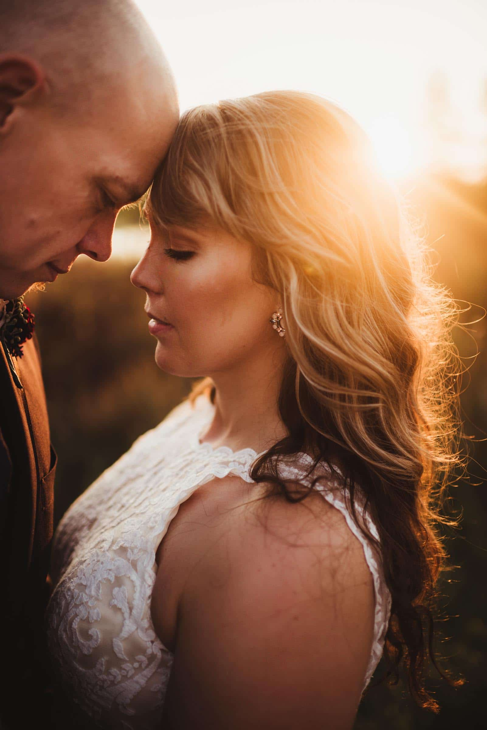 Close Up Bride Groom Touching Foreheads at Sunset