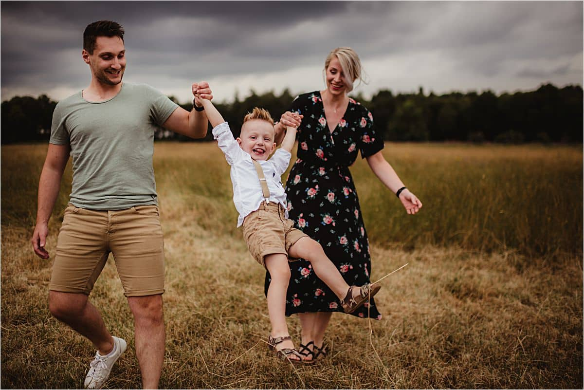 Stormy Skies Family Session Parents Swinging Son