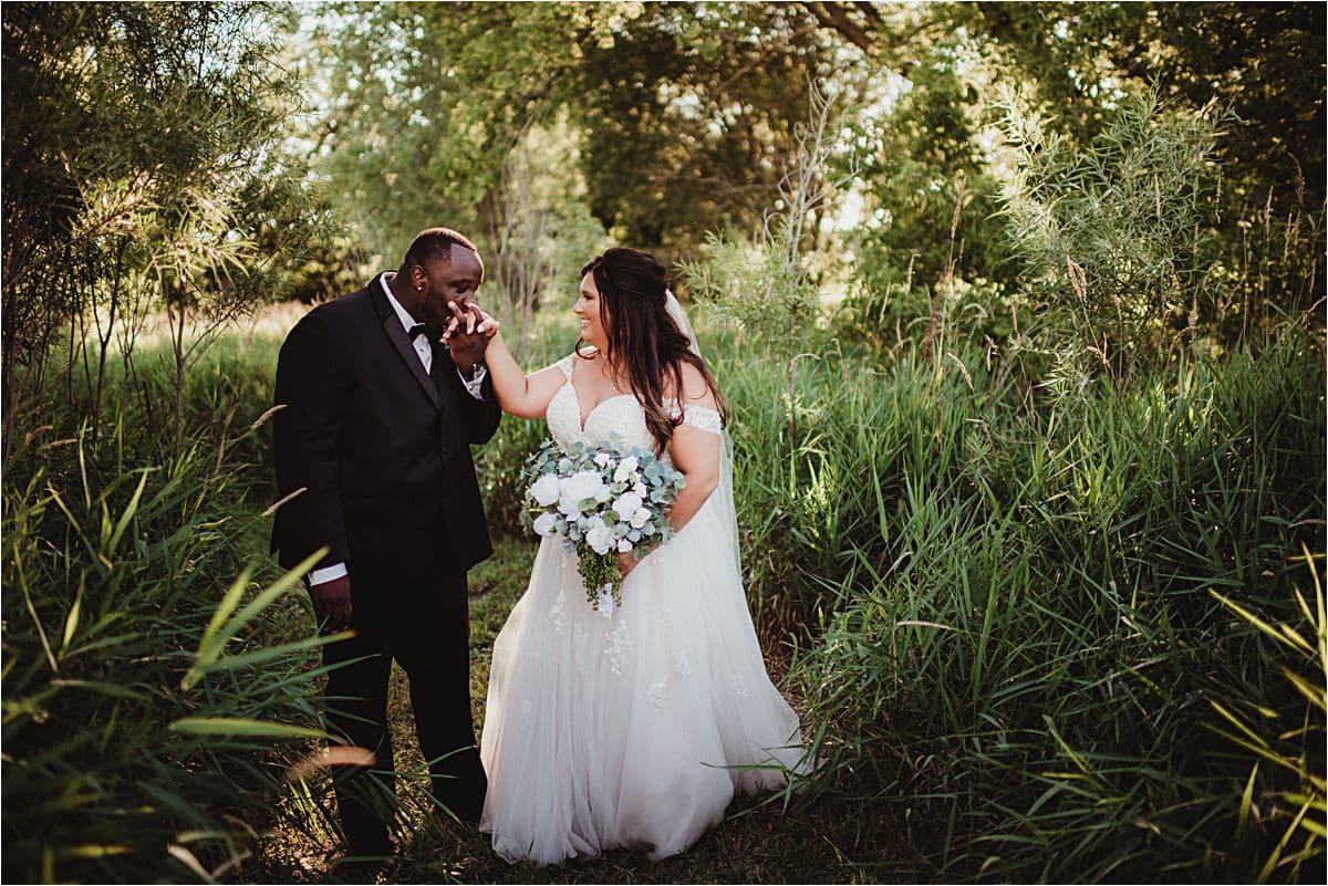 Outdoor Wisconsin Summer Wedding Groom Kissing Bride's Hand