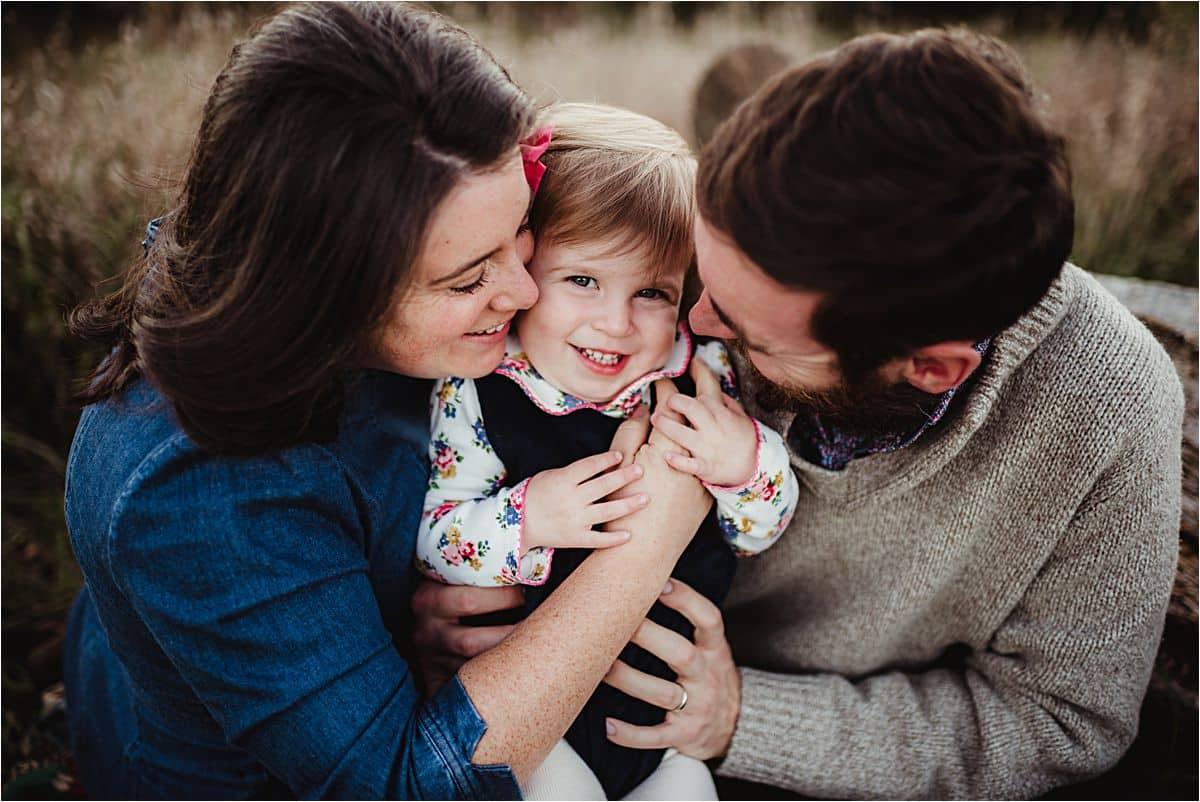 Parents Hugging Smiling Daughter