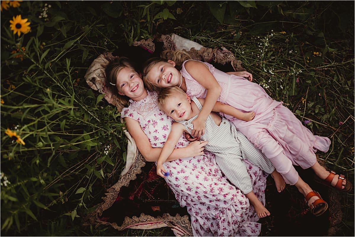 Siblings Laying on Blanket