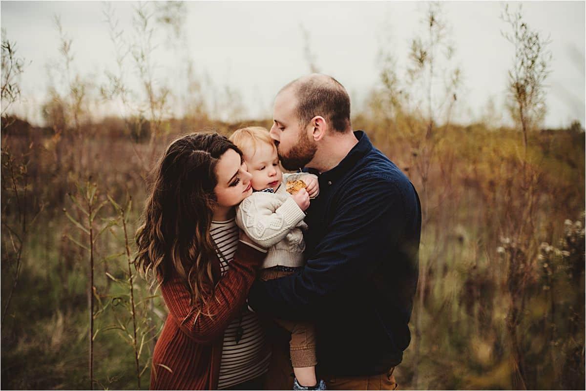 Parents Kissing Son