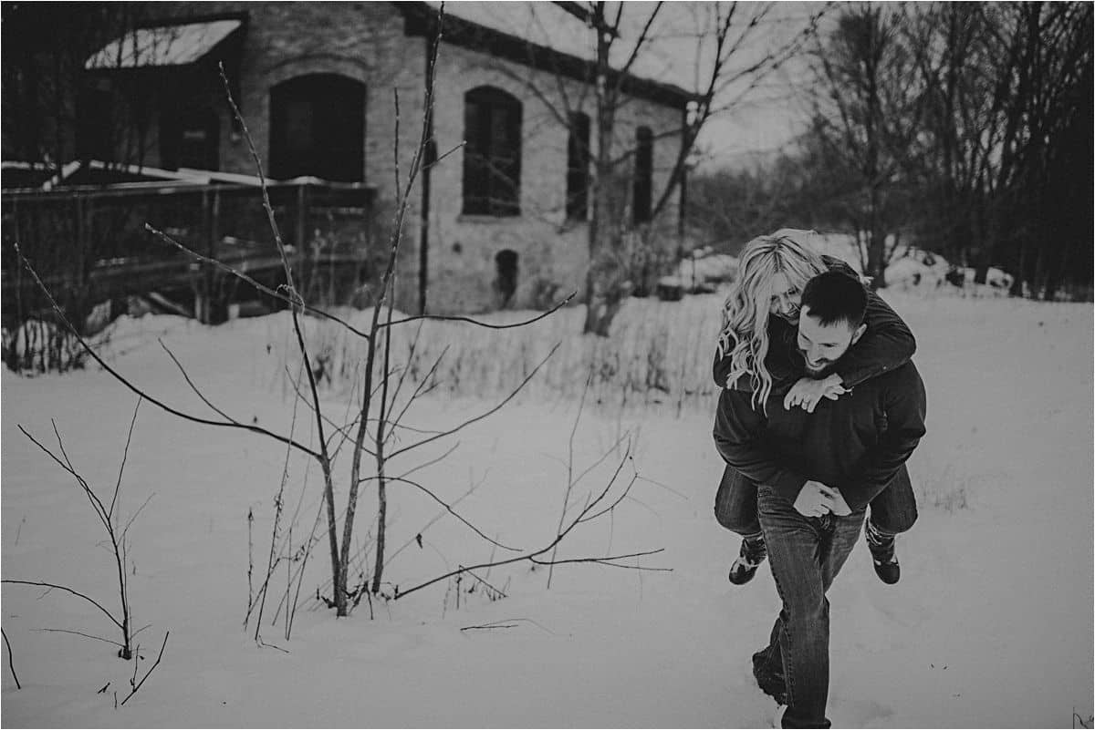 Snowy Winter Engagement Session Woman Getting Piggyback Ride