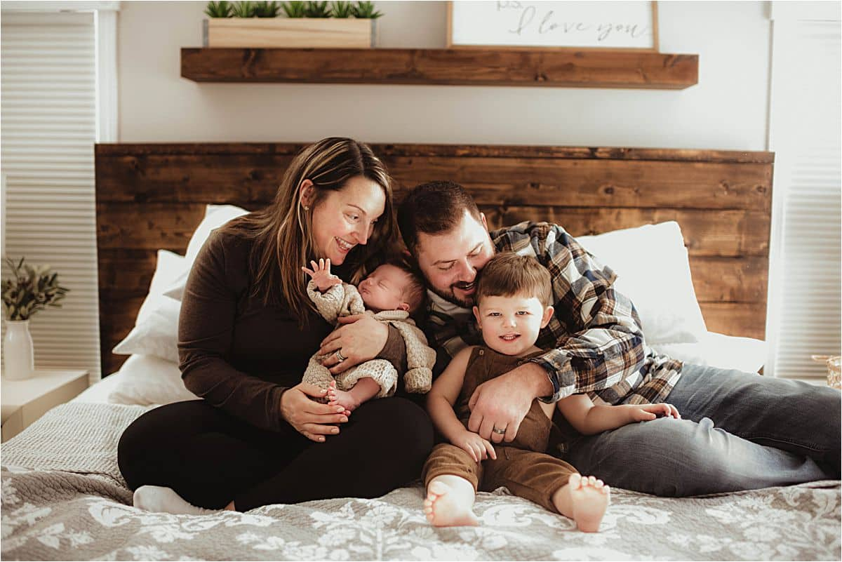 Family with Newborn on Bed