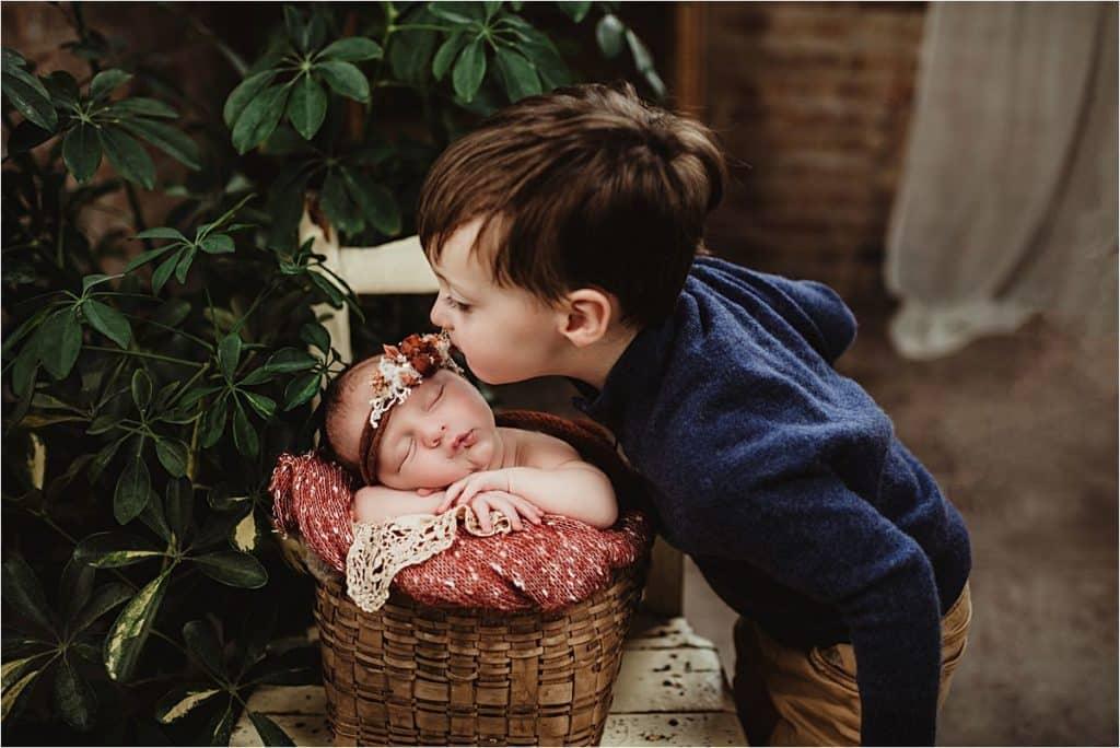 Jewel Tones Newborn Session Brother Kissing Newborn Sister