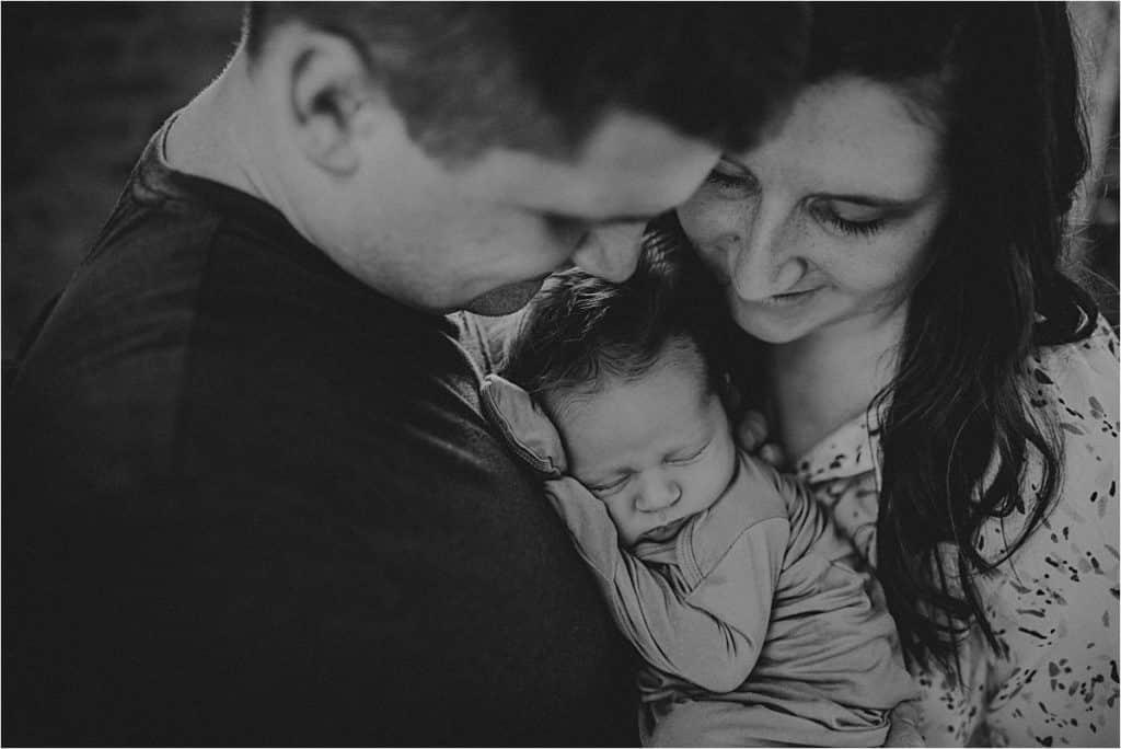 Parents Snugging Newborn Boy