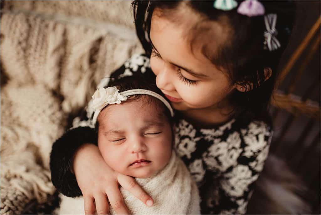 Newborn Photography Session Sister Kissing Newborn