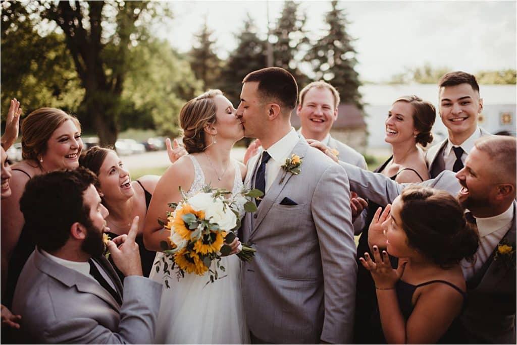 Wedding Party Surrounding Kissing Couple