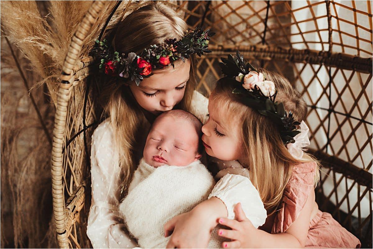 Sisters Kissing Newborn