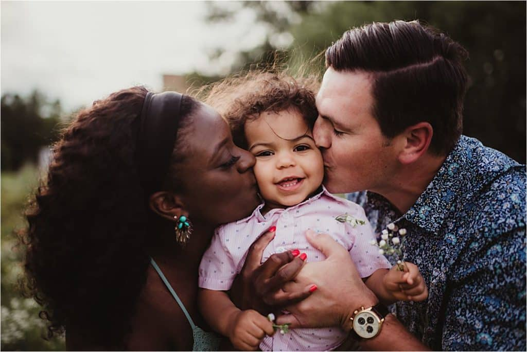 Parents Kissing Son on Cheeks